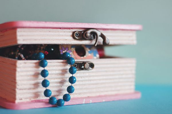 A pink jewelry box with a blue necklace poking out