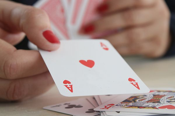Womans hand holding an ace of hearts playing card