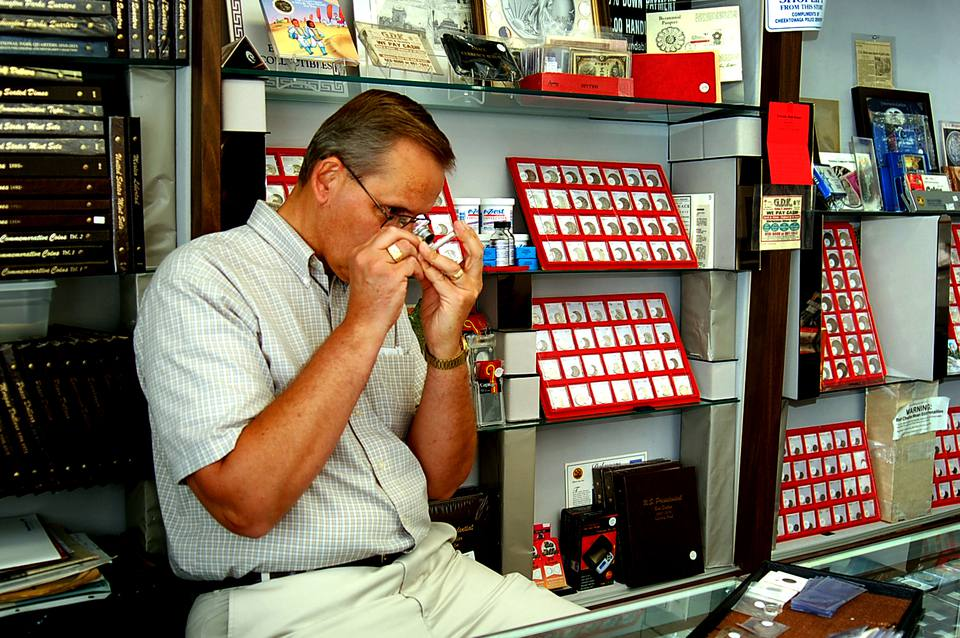 A numismatist inspecting a coin