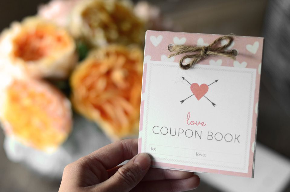 A book of love coupons by a bouquet of flowers