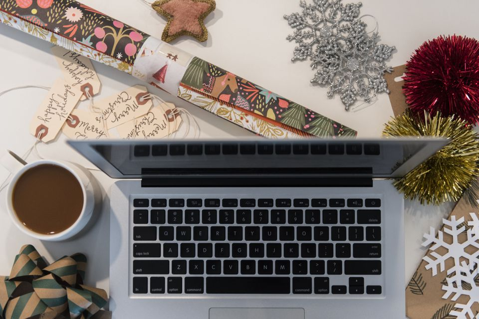 Laptop, coffee, wrapping paper and Christmas ornaments
