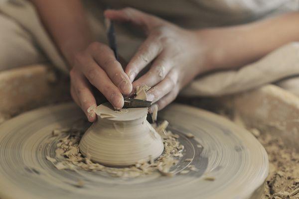 Female potter sharpening bowl in studio