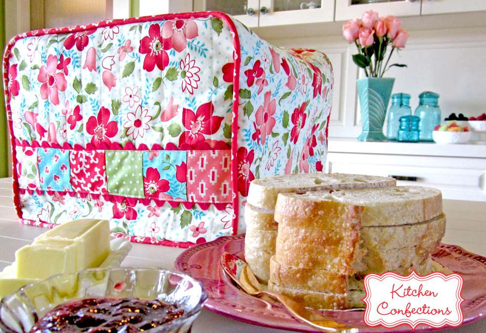 A floral toaster cover with bread, butter, and jam on a kitchen counter