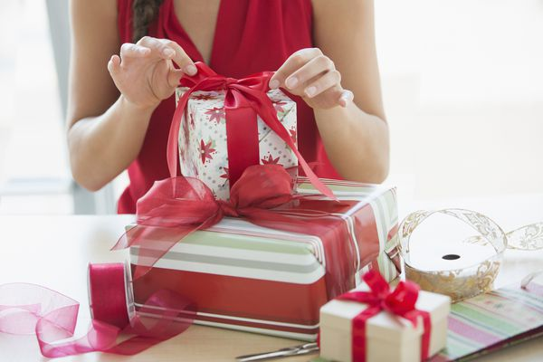 woman tying bow on gift