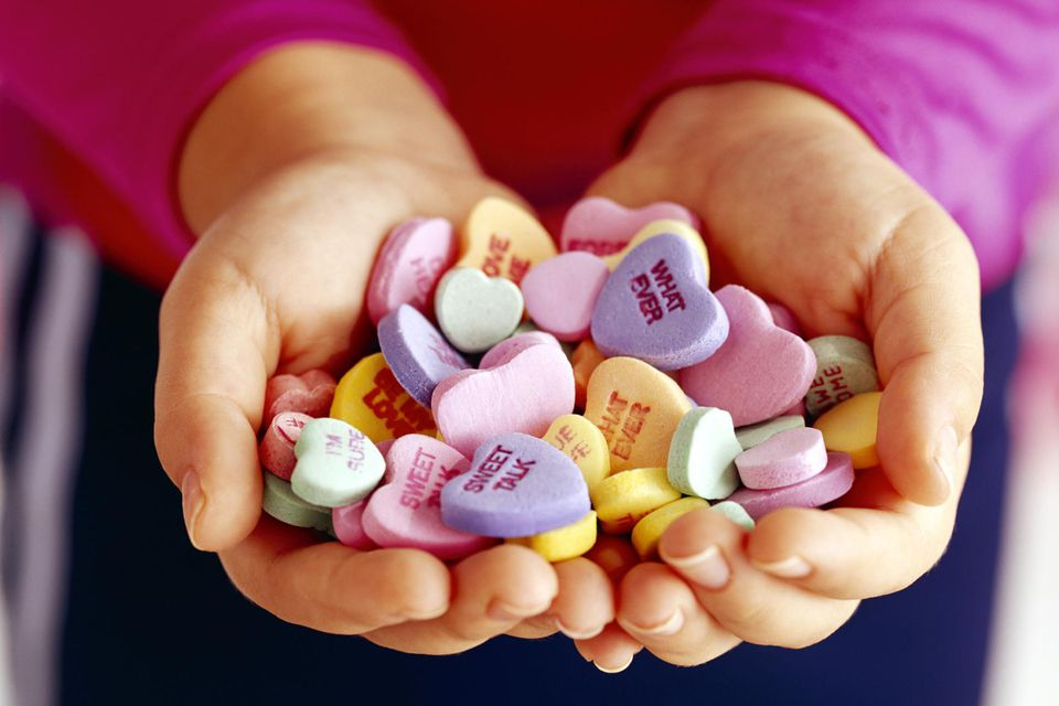 Hands holding candy valentine hearts