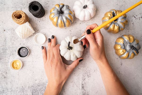 Female hands with black nails painting pumpkins for halloween
