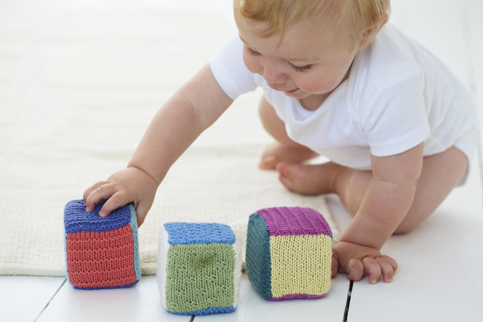 Baby playing with knit blocks