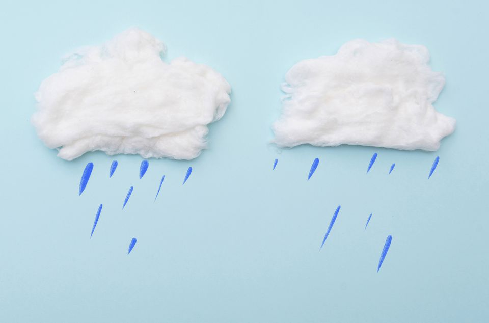 Cumulus clouds by cotton wool with rain drops on blue surface, layout for ideas, space for text