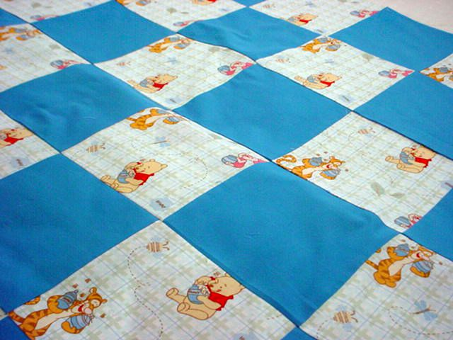 Baby quilt with blue squares and Winnie-the-Pooh squares.