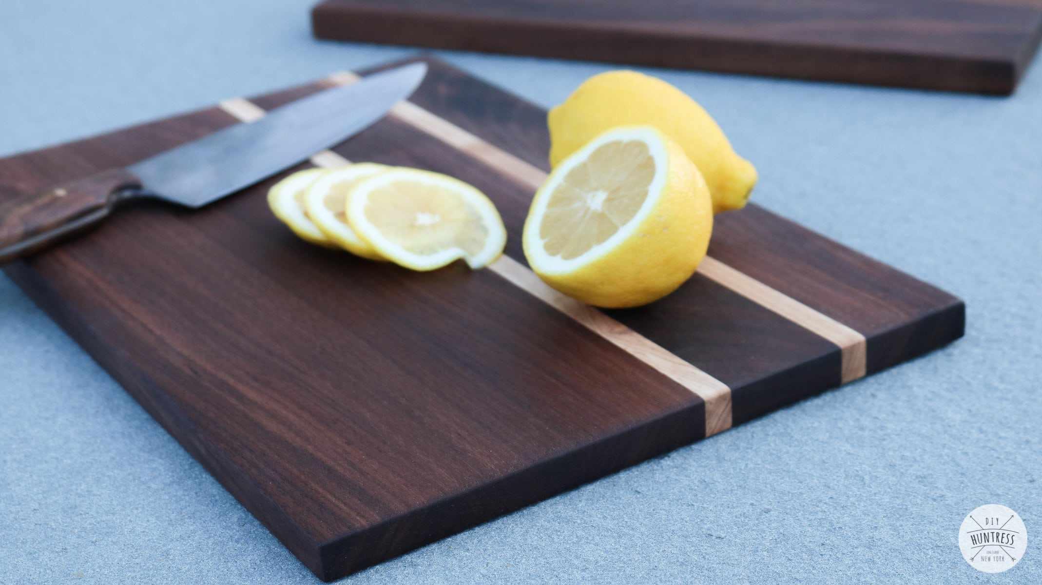A sliced lemon on a dark wood cutting board.