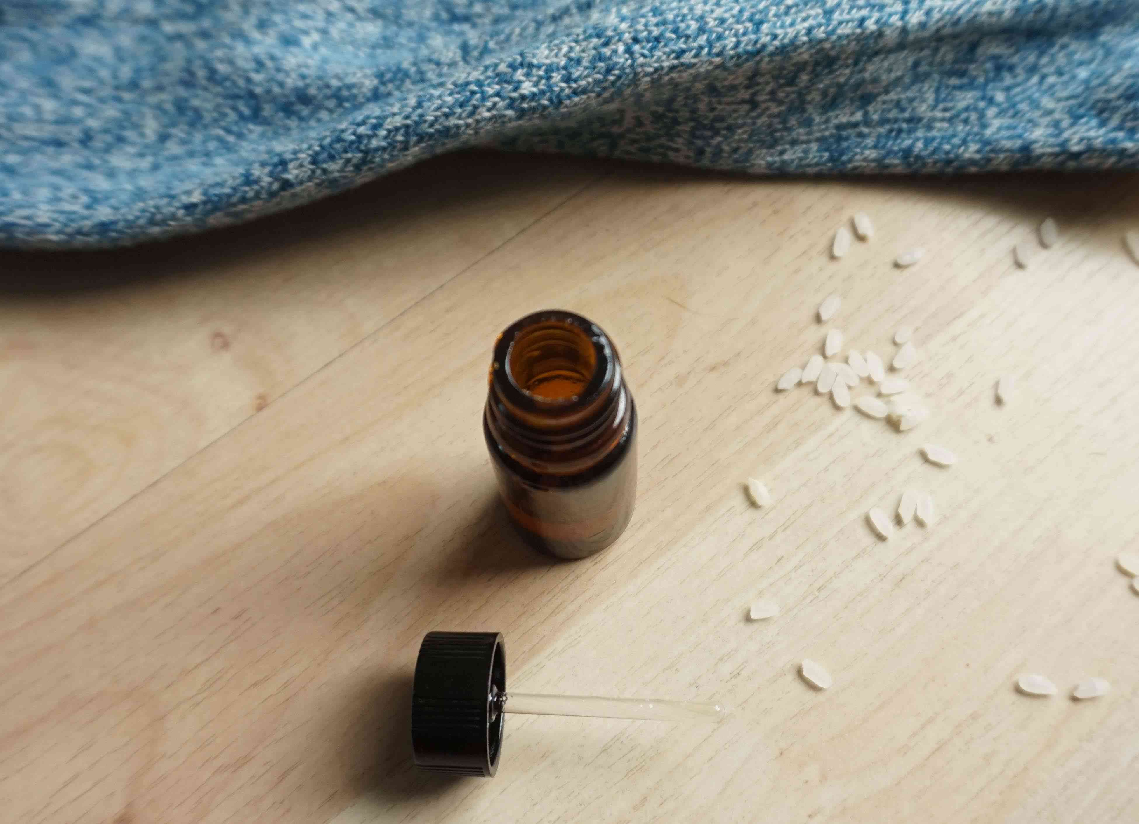 An open bottle of essential oil on a light wood background next to grains of rice and blue fabric.