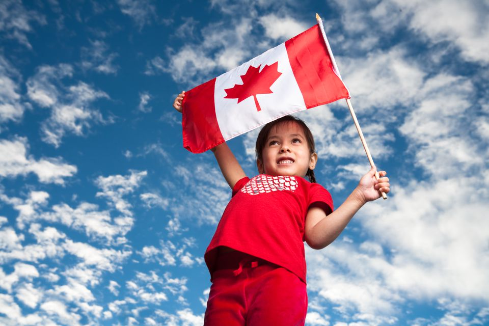 A 5-year-old smiling girl holding a Canadian flag