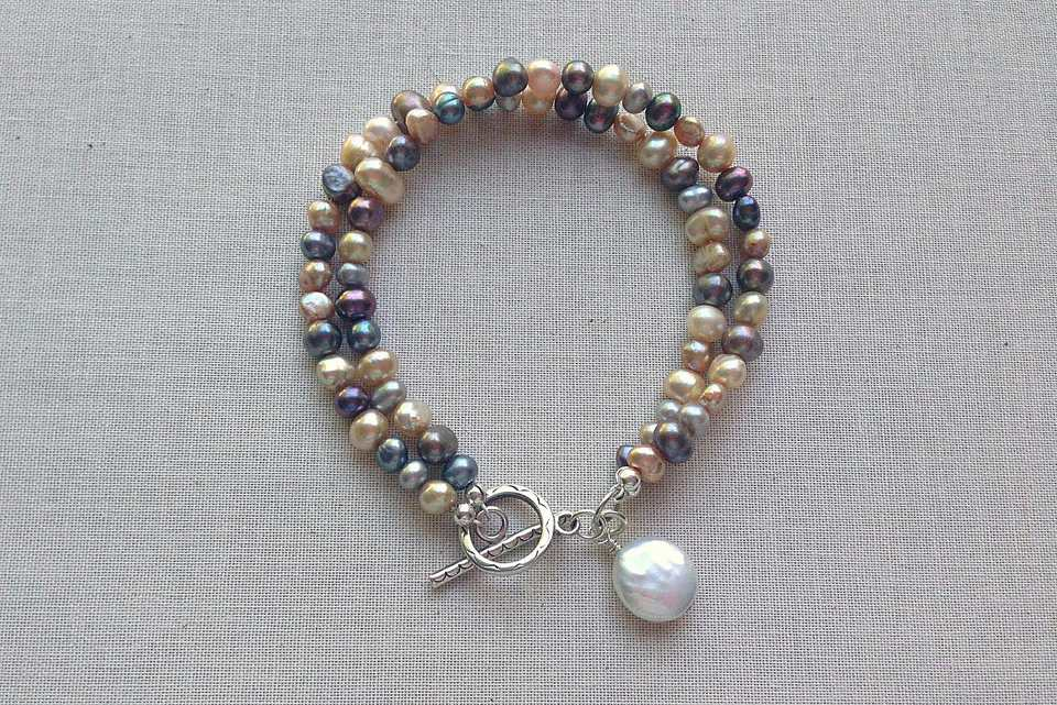 Blue and gold multi-pearl bracelet lying on material.