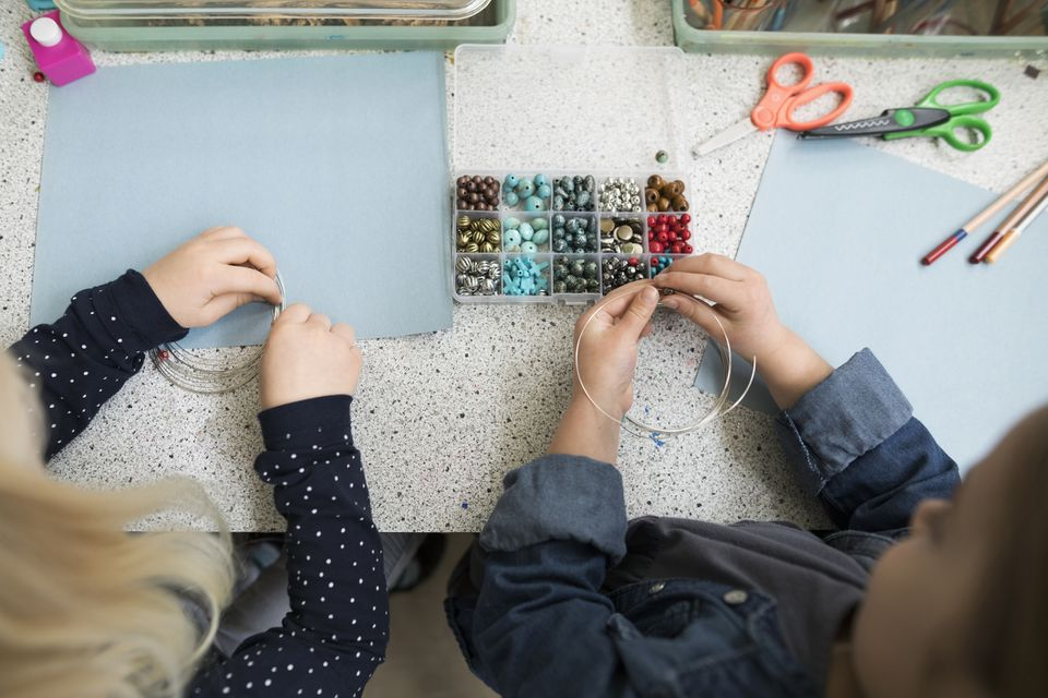 Preschool girls making art and craft project with beads