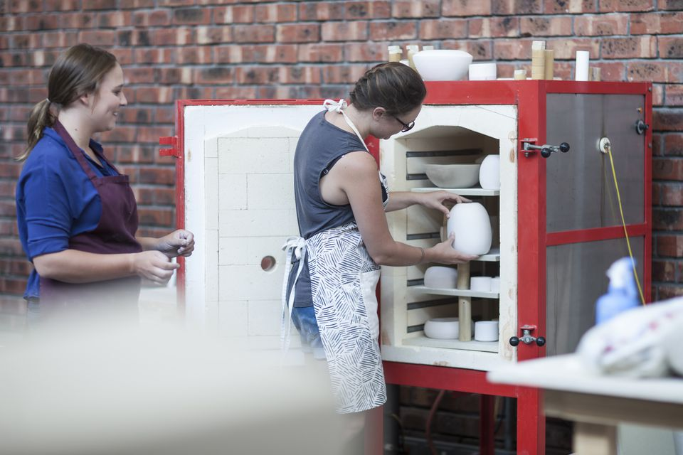 Female potter putting vase into workshop kiln