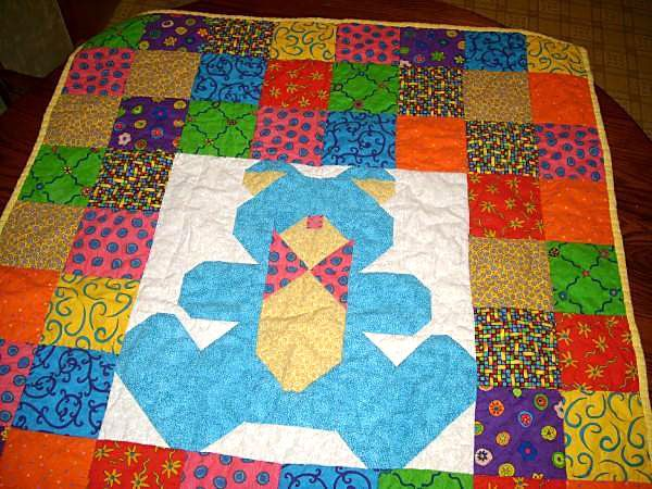 Baby bear quilt with a variety of colorful squares.