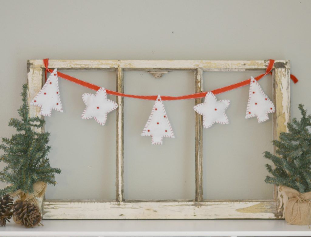 Felt Christmas tree and star bunting hanging across a wooden frame.