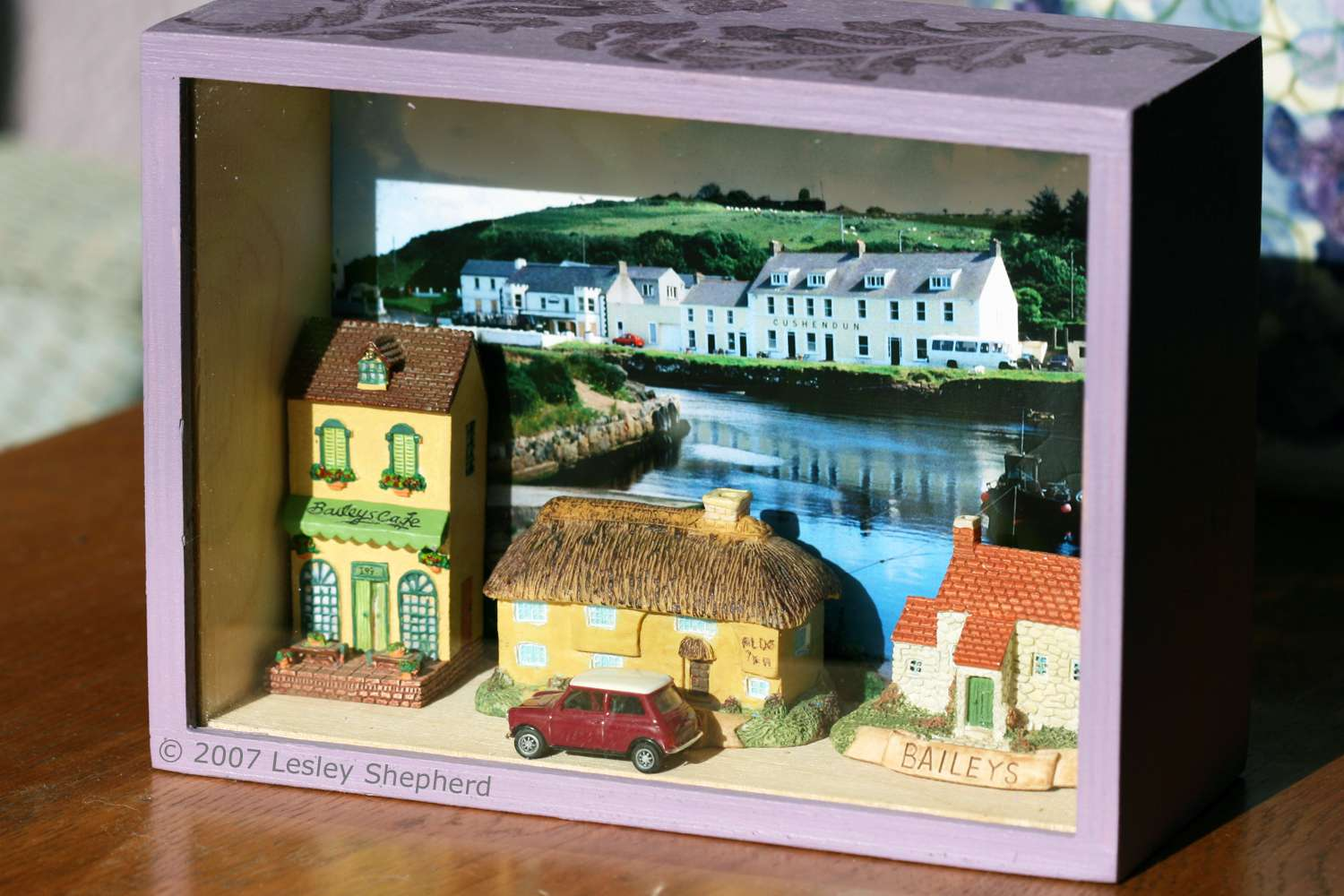 Display box with a collection of miniature Irish cottages against a photo backdrop