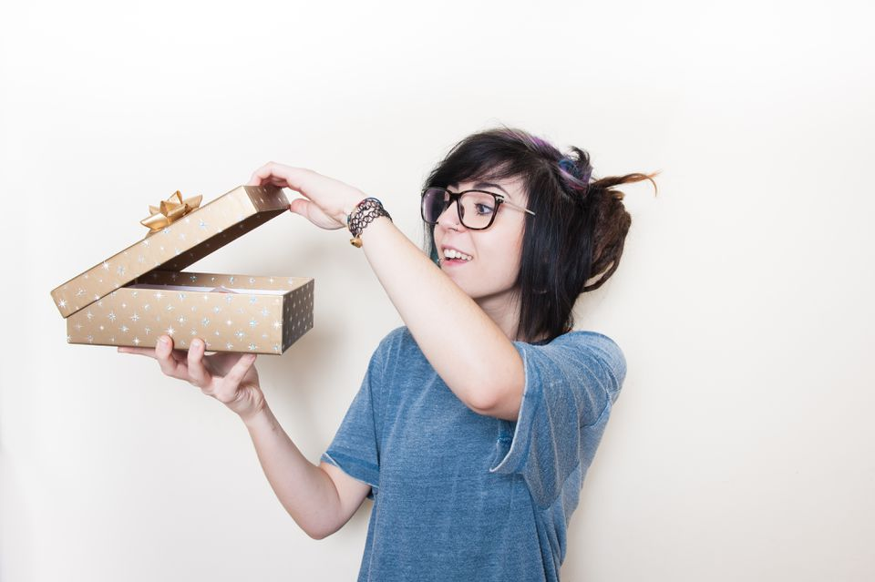 Teenage Girl Opening Gift Box Against White Background