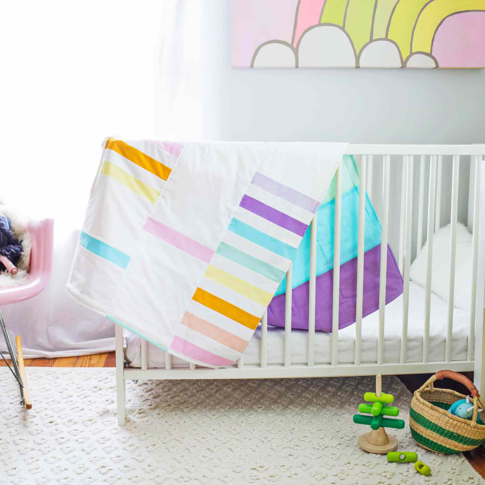 A pastel quilt on a crib