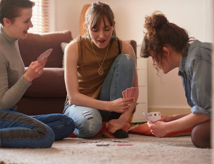 3 girls playing card game in living room