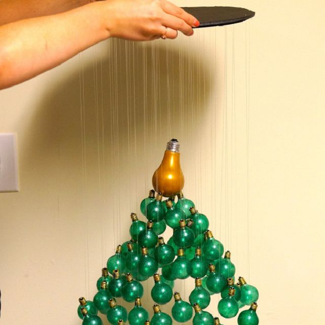 Hands holding up a mobile made from painted light bulbs in the shape of a Christmas tree.
