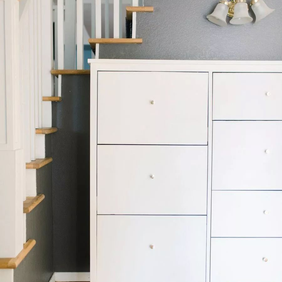A white shoe cabinet by a set of stairs