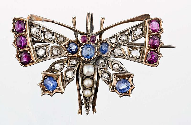 Butterfly pin with old oval cut sapphires and rubies with rose cut diamond and seed pearl accents; in fourteen karat gold and silver.