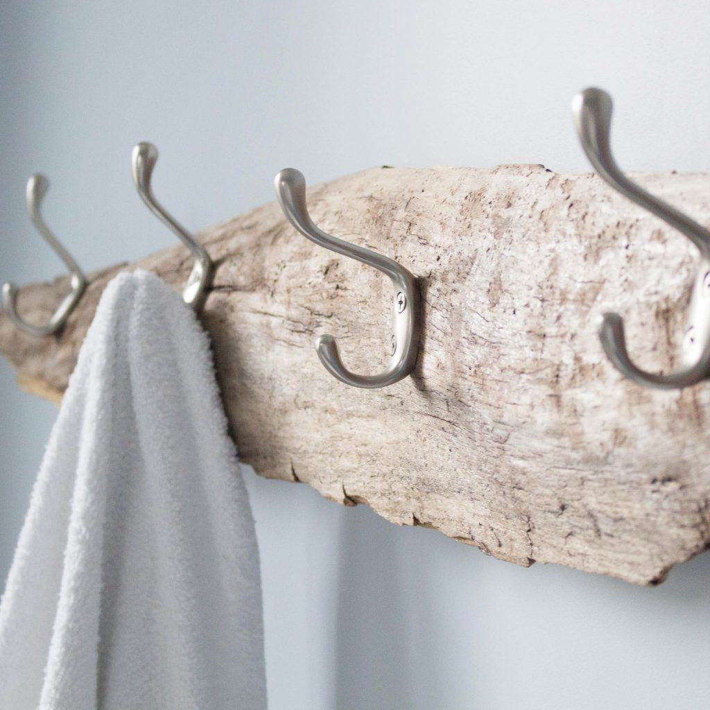 Driftwood with hooks and a towel hanging from them.
