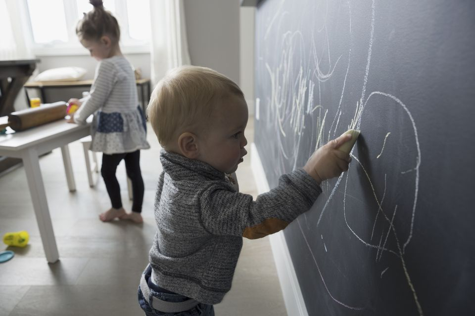 Toddler drawing on a chalkboard