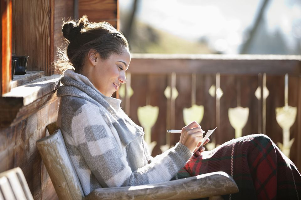 Smiling Woman Solving Word Searches on Cabin Porch