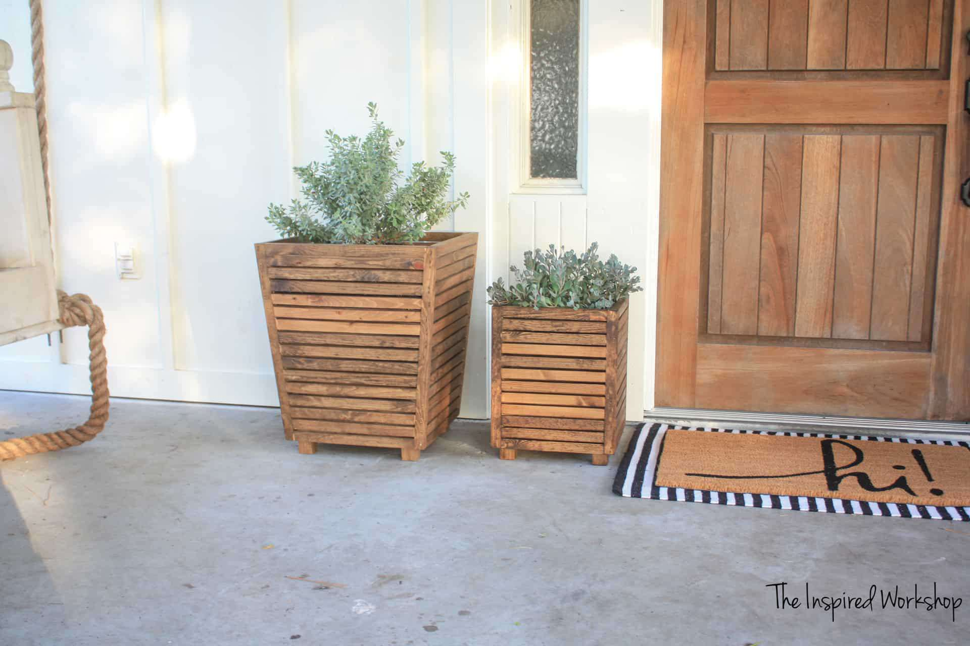 Two wooden planter boxes on a front porch.