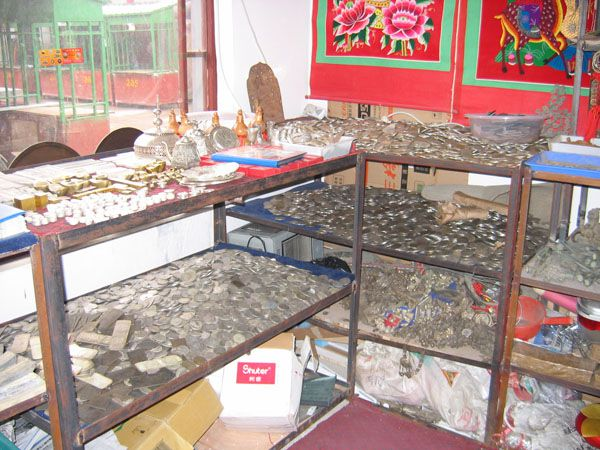 Counterfeit coins, bars, and other small objects can be seen in this showroom in a Chinese coin and antiquities counterfeiting operation.