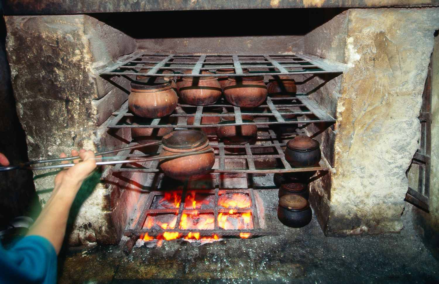 Clay pots cooking over a fire.