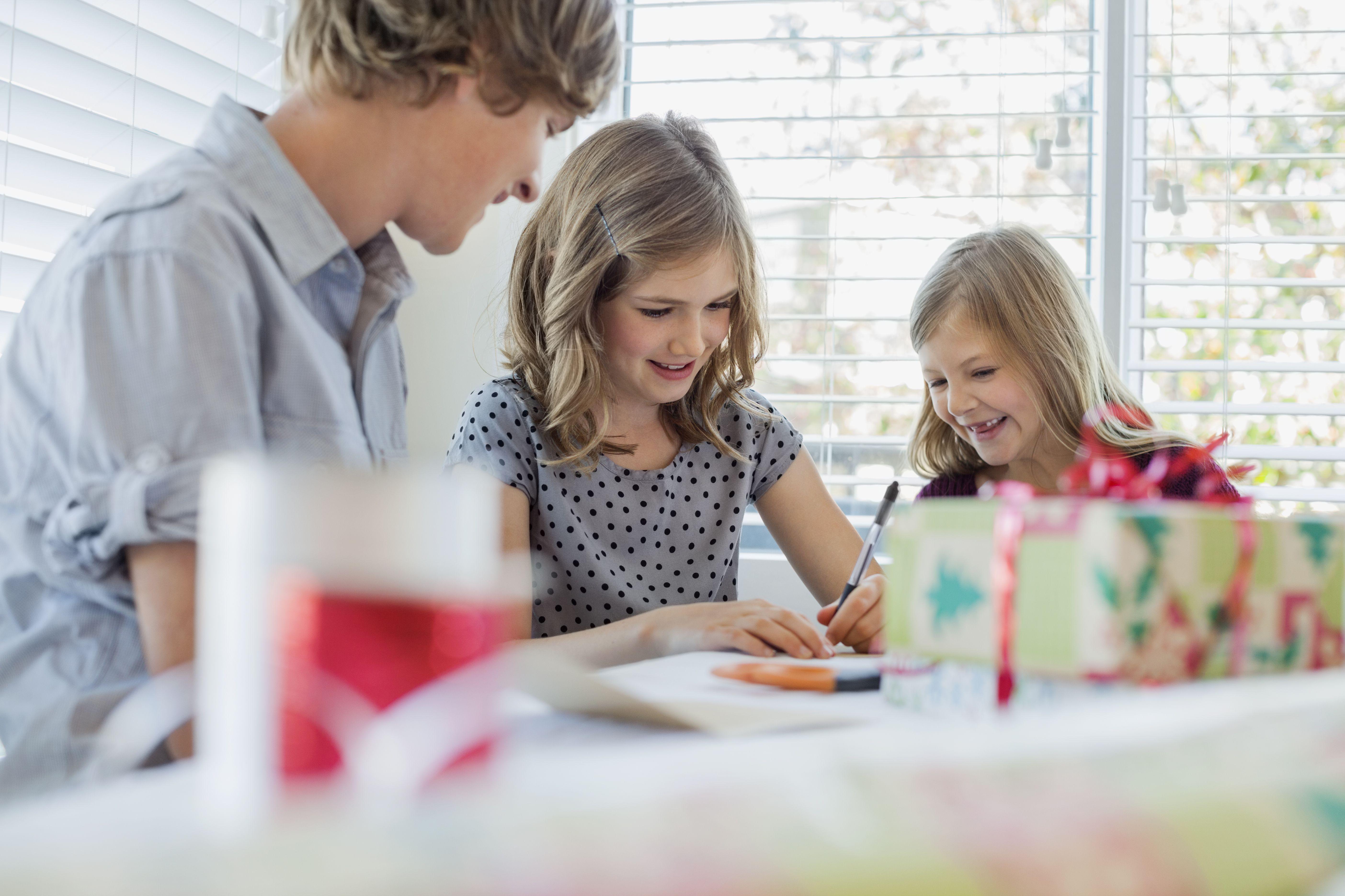 Siblings writing Christmas cards
