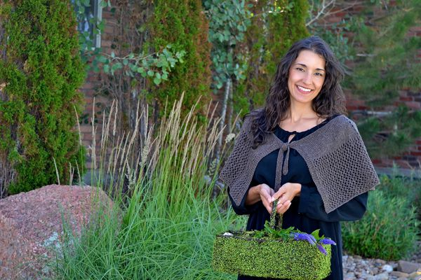 Sassenach Capelet Pattern on a woman carrying a green plant basket