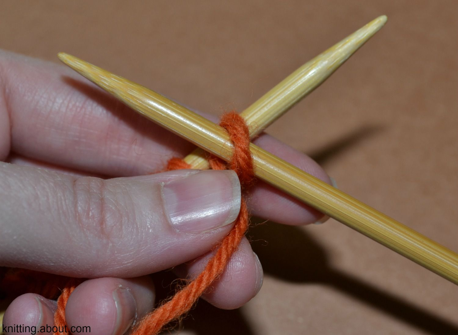 The yarn wrapped over the needle to form a purl stitch.