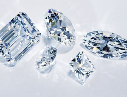 A closeup of five different sized and cut diamonds on a white background