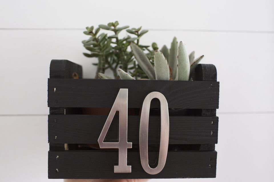 "An image of a small wooden crate painted black with silver numbers that say ""40"" on them. Succulents are inside the crate."