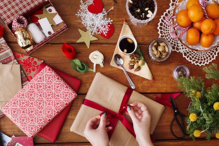 Cropped Image Of Hands Tying Bow On Christmas Present At Wooden Table