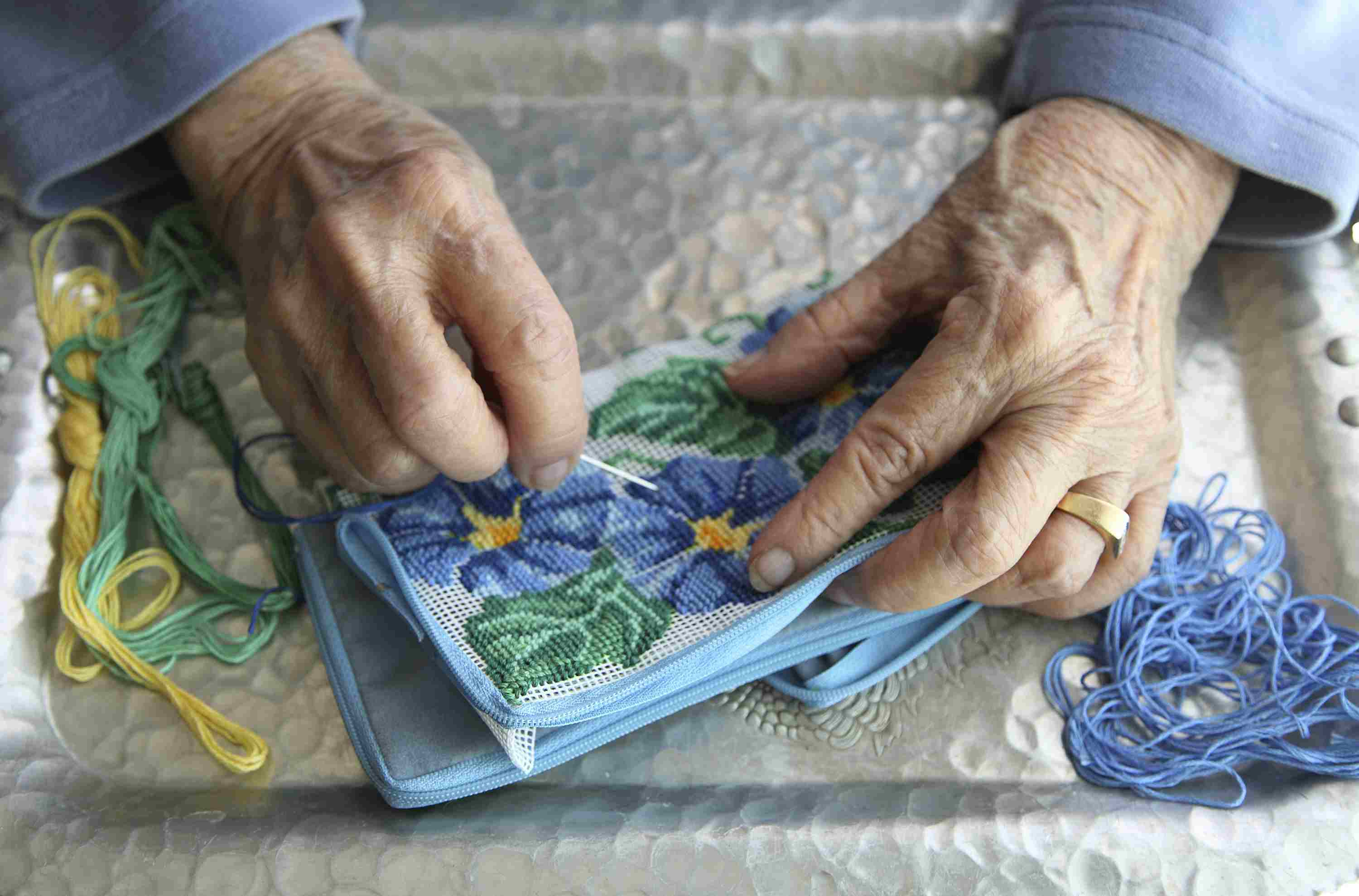 woman stitching needlepoint