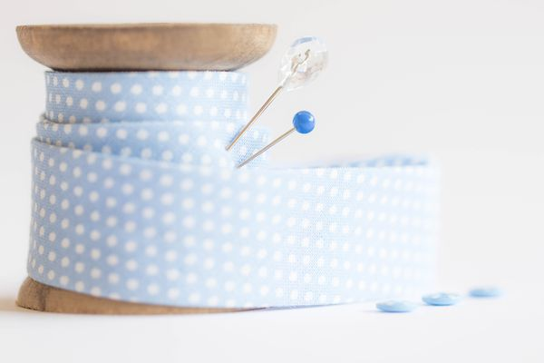 Blue and white spotted bias binding on spool with pins