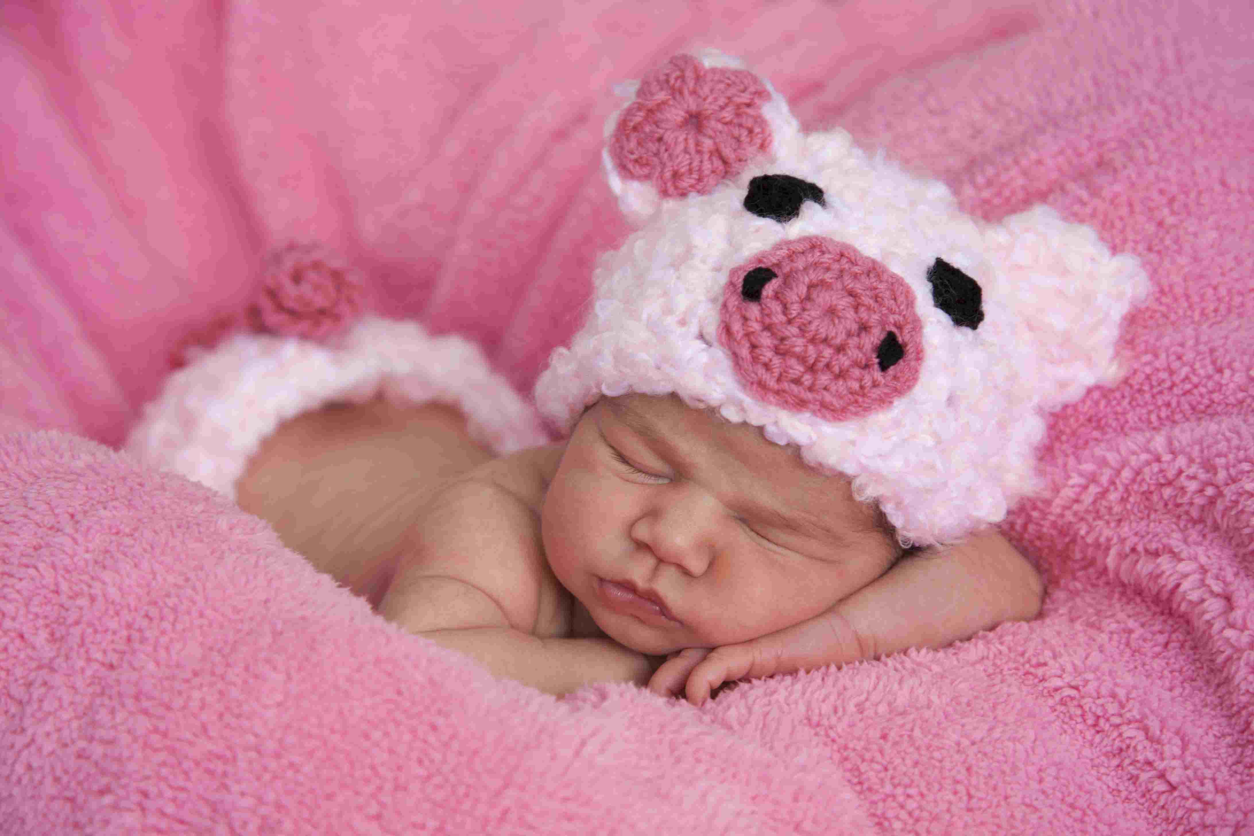 Newborn baby girl dressed in pink piggy outfit