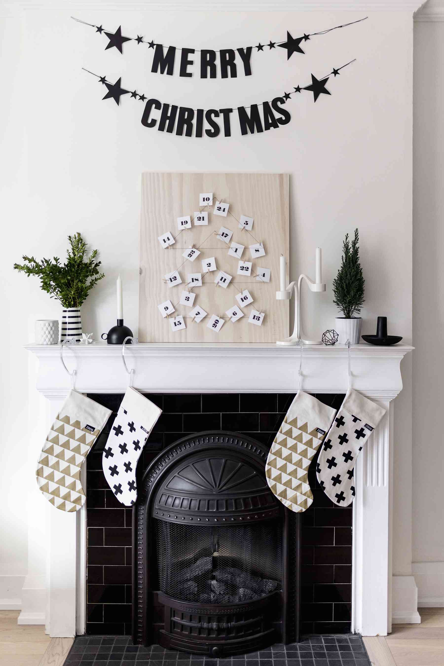 Modern black and white advent calendar on a board sitting on a mantle.