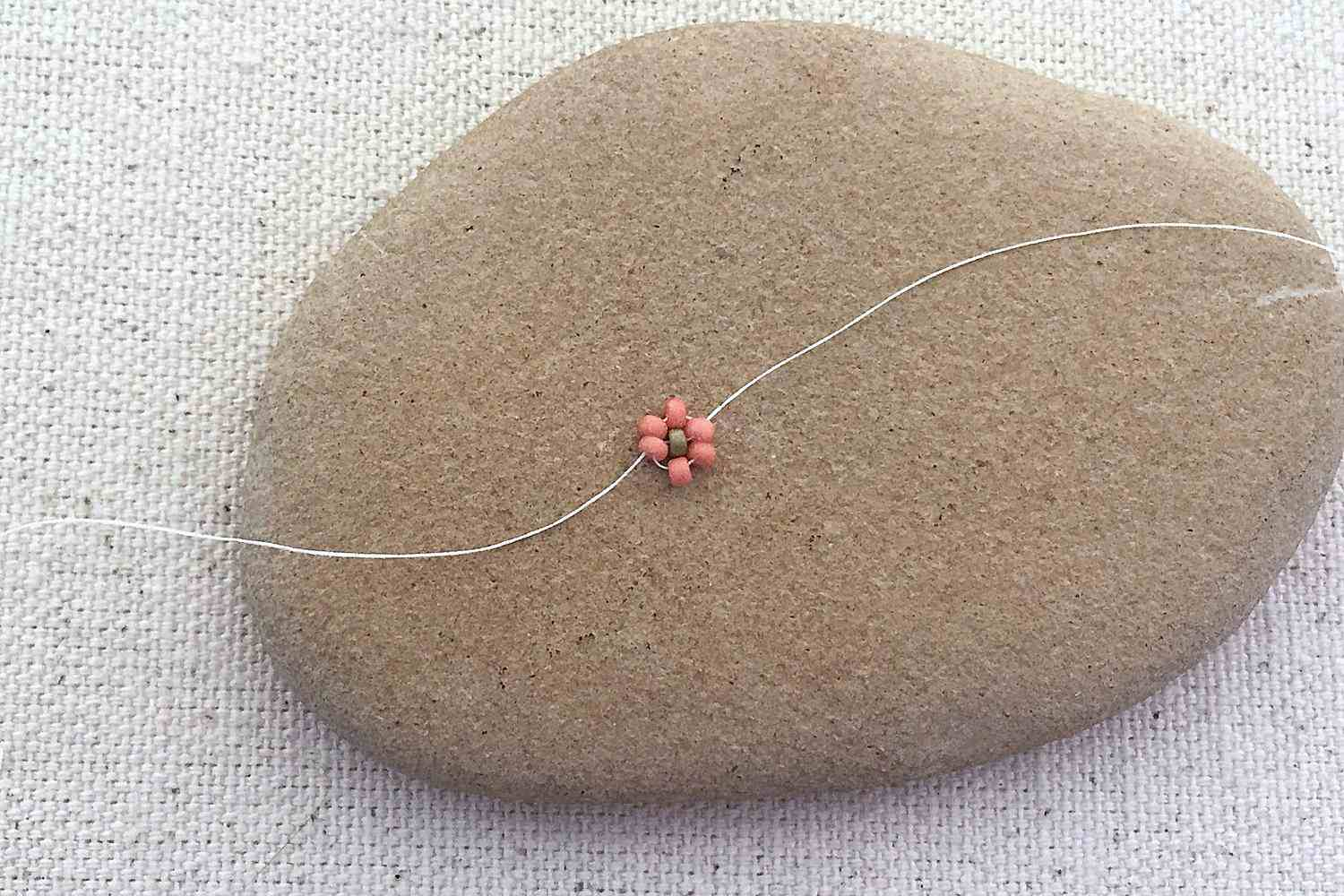 Pulling thread tight to arrange the petals and daisy center