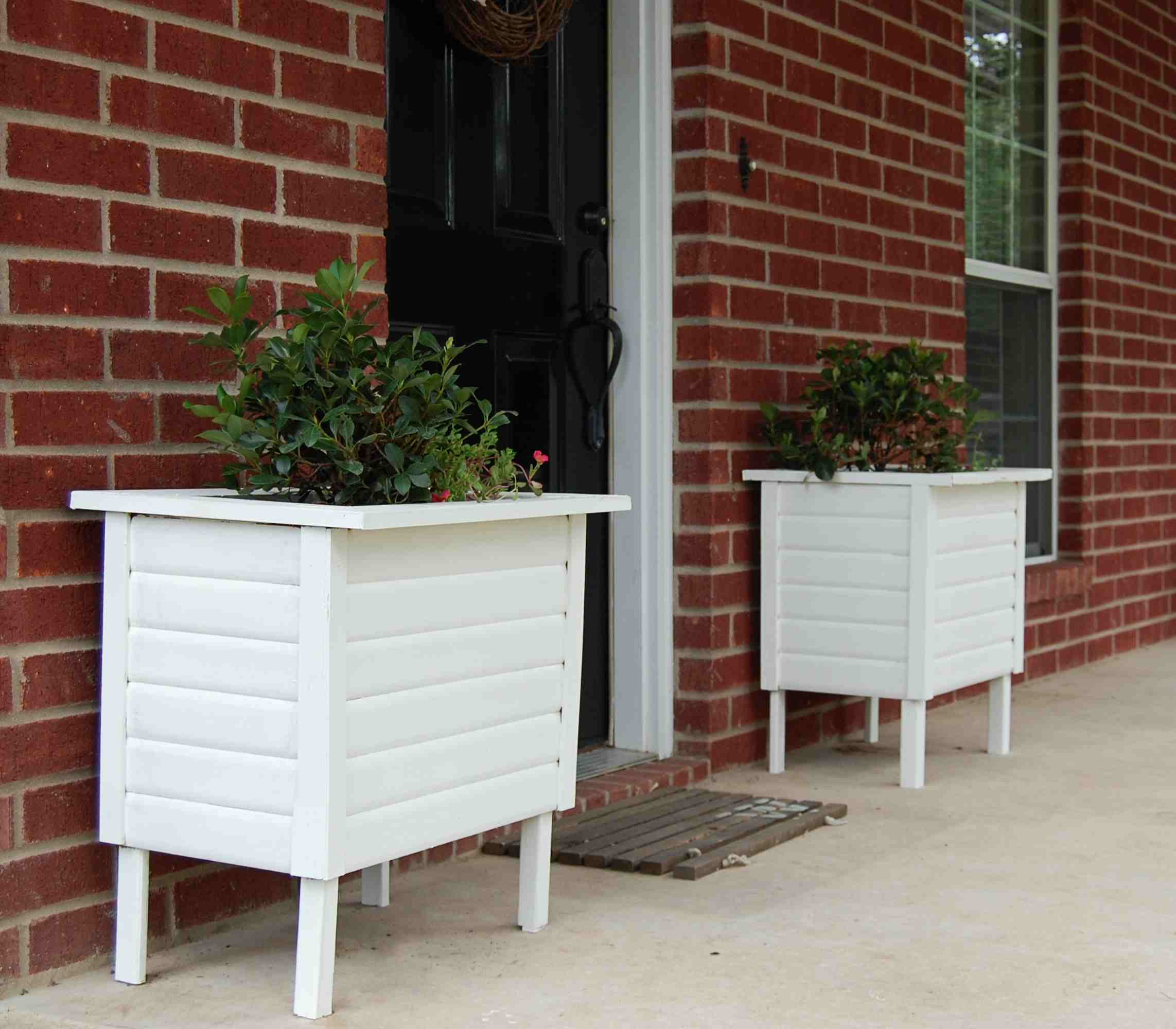 Two white planters by a front door
