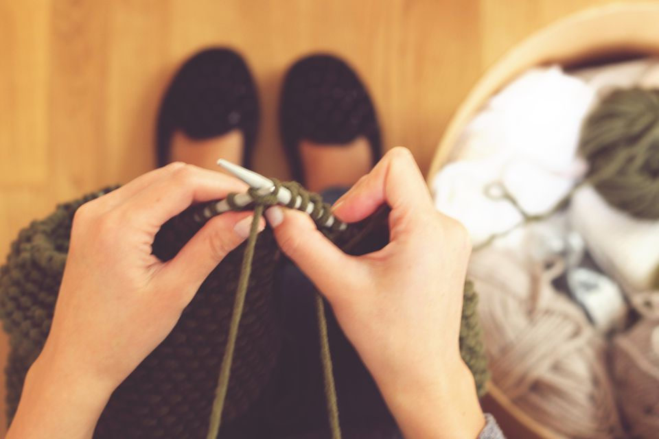 An image of a woman's hands knitting wool