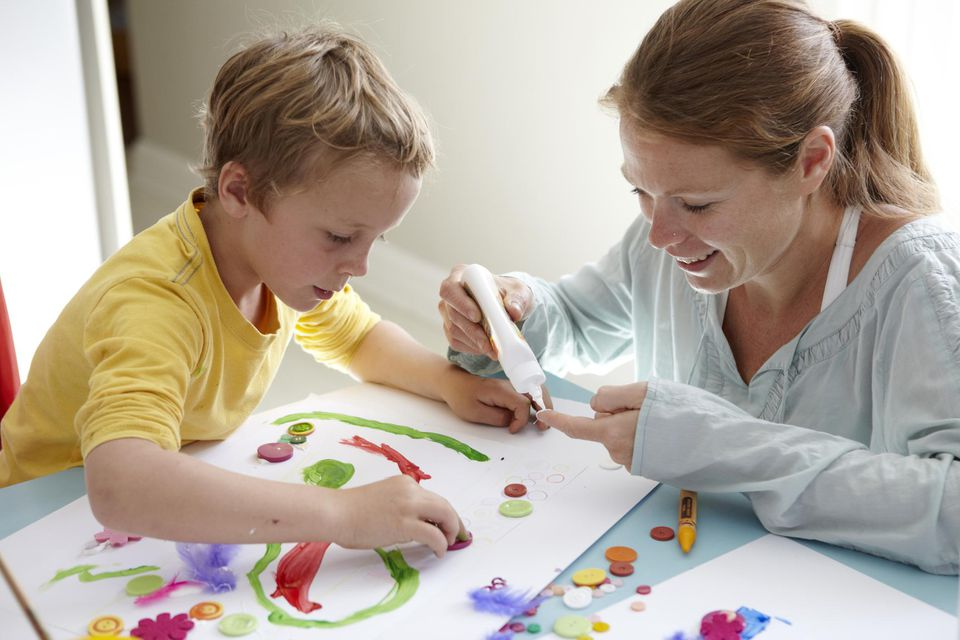 Child painting a picture with his mother.