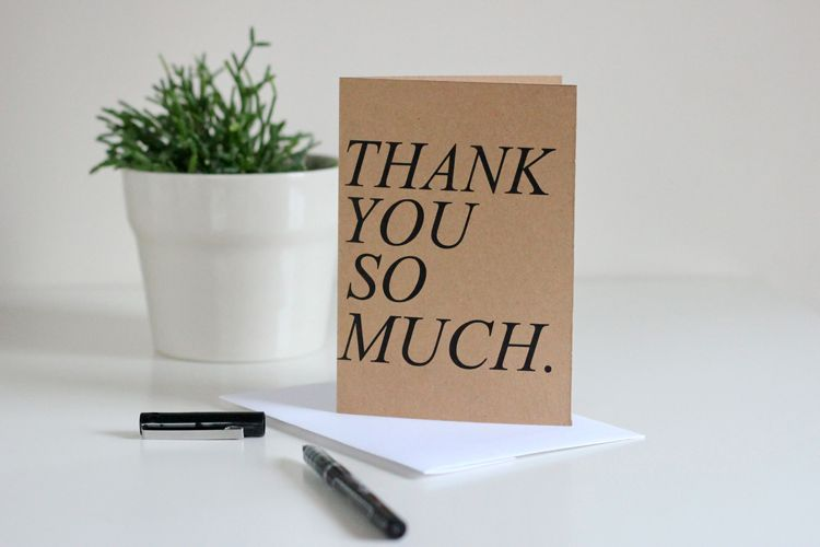 "A card that says ""Thank You So Much."" sitting upright on a table."