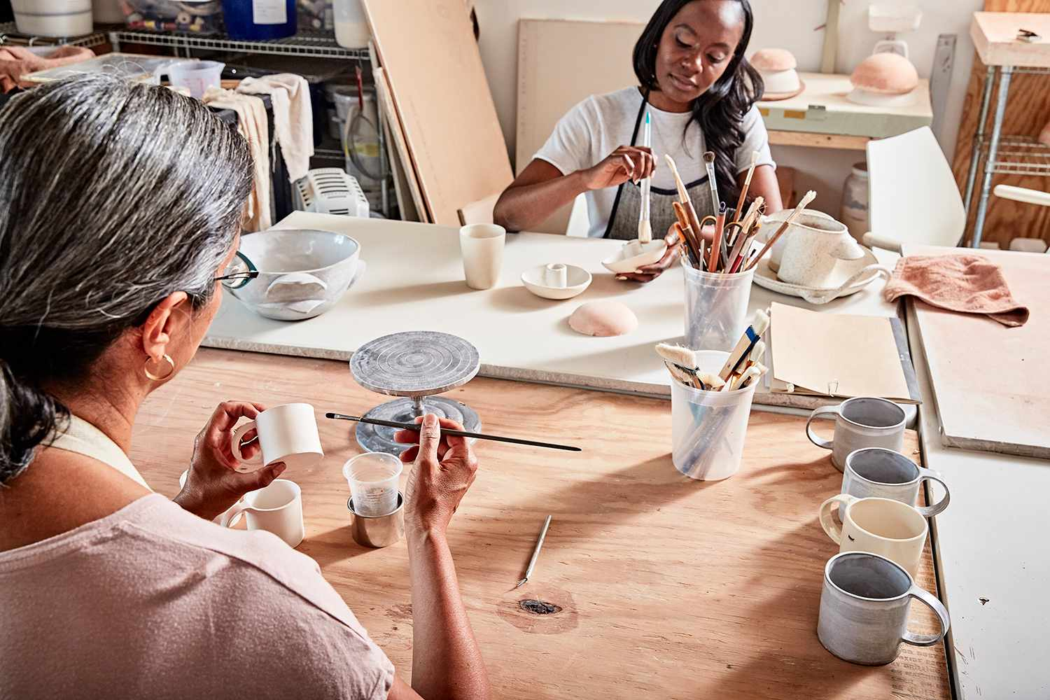 Potters in workshop painting pottery